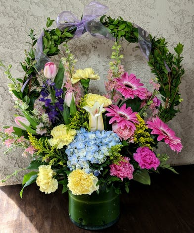 Pink, purple and blue arranement accented with a myrtle arch and lavender ribbon designed in a leaf-lined vase.