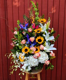 Sunflowers, roses, hydrangea, dendrobium orchids, irises, snap dragons, bells of Ireland, and stargazer lilies in a ceramic vase.