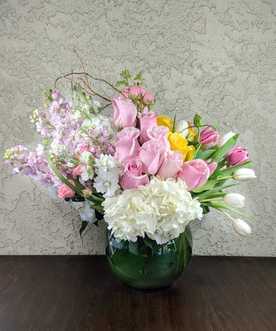 Pink roses, white and pink stock, yellow roses, white and pink tulips, white hydrangea, and pink spray roses accented with curly willow and bear grass in a glass fish bowl.