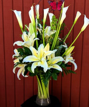 Bouquet of white stargazer lilies and white calla lilies with butterfly decoration in a clear glass vase.