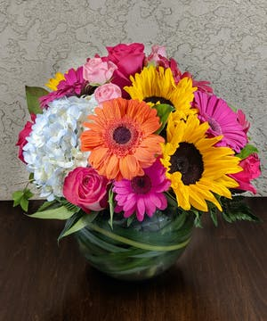 Gerbera daisies, sunflowers, and spray roses with hydrangea in a leaf-lined bubble bowl vase.