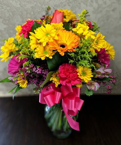 Yellow, pink and orange flowers with greenery in a clear glass vase tied with pink ribbon.