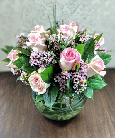 Roses and waxflower with bear grass in a compact fish bowl design.