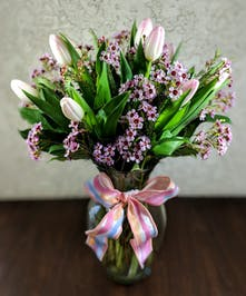 Ten stems of tulips arranged in a clear glass vase with waxflower and tied with a bow.