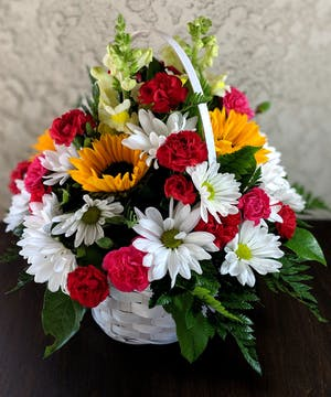 Long-lasting bouquet of hot pink and red mini carnations, white chrysanthemum daisies, yellow sunflowers and yellow snapdragons in a white wicker basket.
