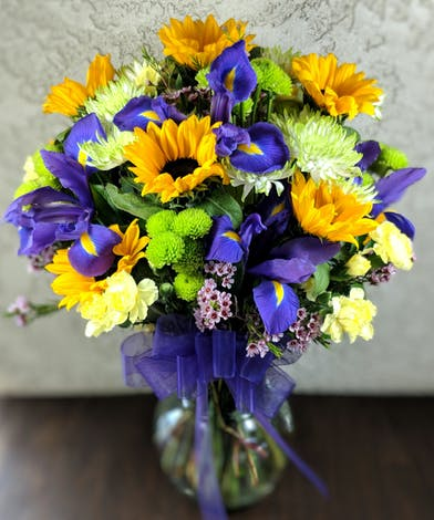 Purple irises, yellow sunflowers, yellow mini carnations, green chrysanthemums and green button mums in a clear glass vase tied with purple ribbon.