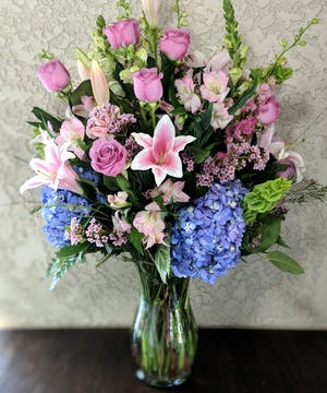 Clear glass vase filled with pink stargazer lilies, lavender roses, blue hydrangea, pink alstroemeria, yellow snap dragon and green bells of Ireland