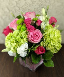 Green hydrangea, pink roses and more in a pink glass cube vase.