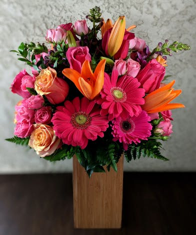 Pink, orange and red flowers in a wooden block vase.