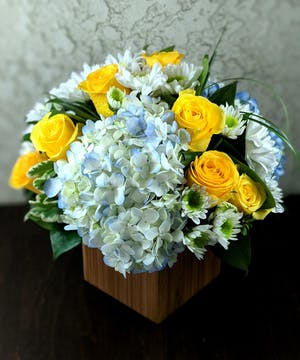 Blue hydrangea, yellow roses and greenery in a wooden block vase.