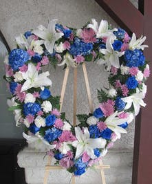 Sympathy heart wreath of white stargazers and carnations, blue roses adn hydrangea, and lavender chrysanthemums.