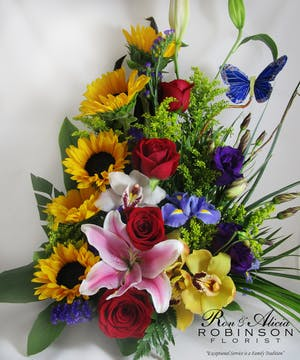 Sunflowers, red roses, iris, cymbidium orchids, purple lisianthus and a pink lily in a one-sided floral arrangement.