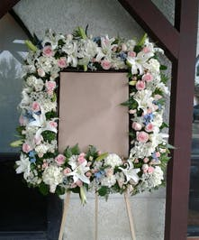Floral wreath of pink, white and blue flowers to surround a photograph.