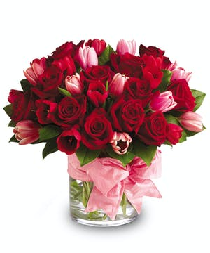 Red and pink mini roses and tulips in a clear glass cylinder vase wrapped in a pink ribbon.