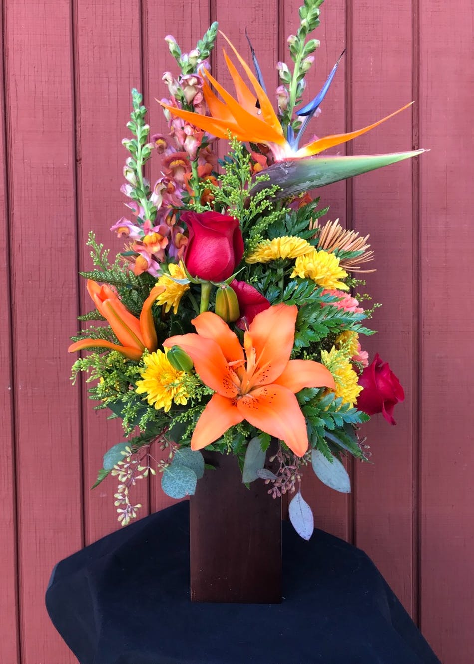 Fall flower arrangement of orange lilies, red roses, yellow chrysanthemum, spider nums, orange snap dragons and birds of paradise.