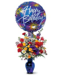 Birthday flower bouquet of red, yellow, orange and purple flowers in a blue vase with happy birthday mylar balloon.