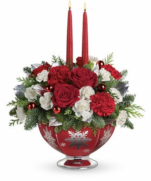 Red bowl with silver snowflakes hold red and white flowers and winter greenery with two taper candles.
