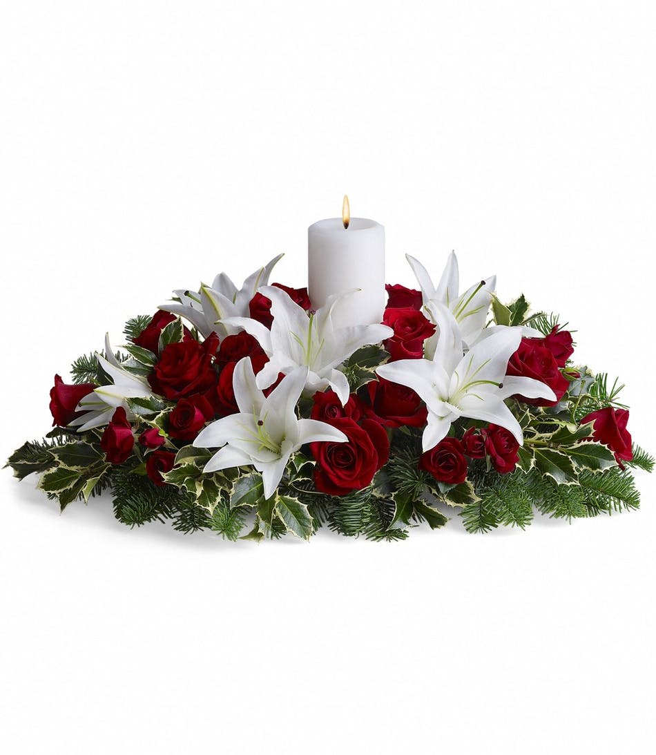 Holiday centerpiece of red roses, white lilies, and winter greenery with a white pillar candle.