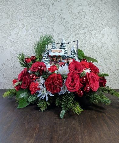 Centerpiece of red flowers, winter greenery and more with a Thomas Kinkade Family Tree keepsake.