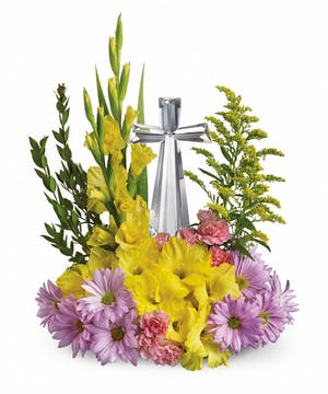Crystal cross keepsake surrounded by pink and yellow flowers.
