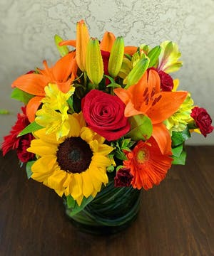 Sunflowers, orange lilies, red roses and more in a leaf-lined glass vase.