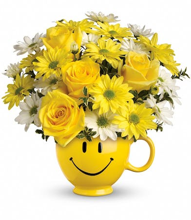 Yellow roses and daisies in a yellow smiley face mug