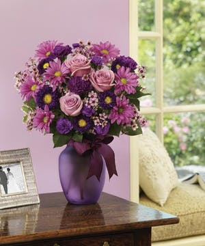 Bouquet of lavender, lilac and violet colored flowers in a purple glass vase.