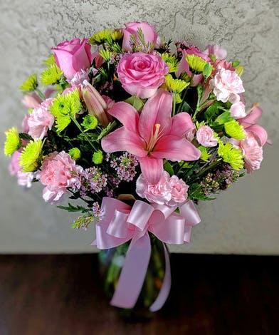 Pink lilies, green button mums, pink carnations, pink roses and mini carnations in a clear glass vase tied with pink ribbon.