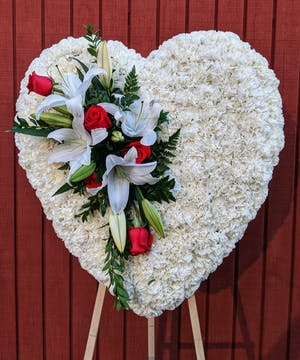 Sympathy heart of all white carnations accented with red roses and white stargazer lilies.