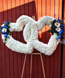Sympathy design of two hearts made of white carnations with blue rose accents.