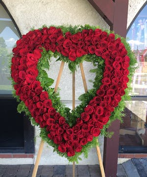 Sympathy heart of red roses and greenery presented on an easel.