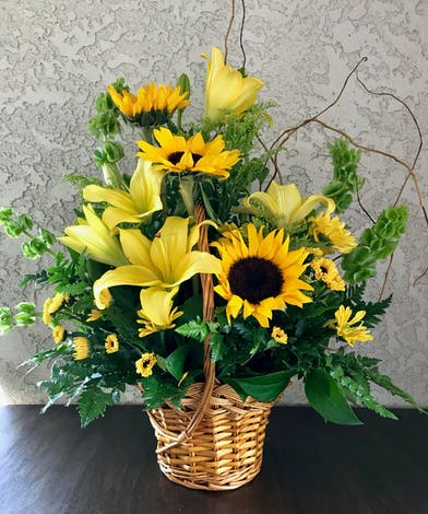 Sunflowers and yellow tiger lilies in a wicker hand basket.