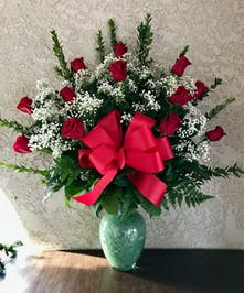 One dozen roses, baby's breath and greenery in a turqouise vase.