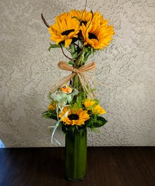 Topiary of sunflowers, greenery and curly willow in a glass vase.