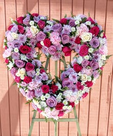 Sympathy heart arrangement of hot pink, lavender and white flowers and greenery.