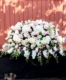 Casket spray of pink roses, pink and white larkspur, and more.