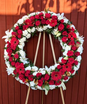 Sympathy wreath of red gerbera daisies, roses, white carnations and white lilies.