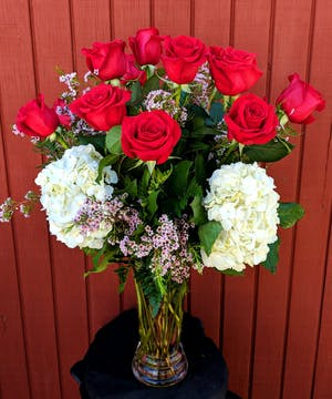Long stem Ecuadorian roses and hydrangea in a clear glass vase.