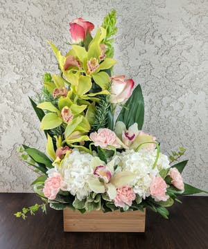 Cymbidium orchids, hydrangea, and carnations in a natural bamboo box.