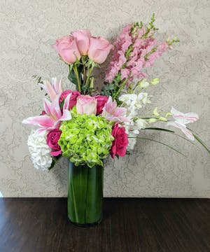 Roses, hydrangea and snapdragons in a leaf-lined vase.