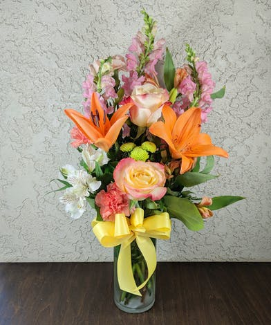 Snapdragons, tiger lilies, roses, carnations, alstroemeria and button mums in a clear glass vase tied with yellow ribbon.