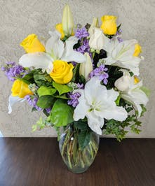 Yellow roses, white lilies and lavender stock in a clear glass vase.