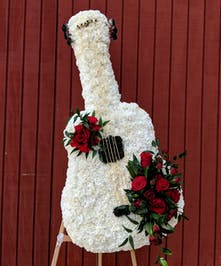 A lovely funeral arrangement designed in the shape of a guitar!