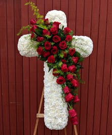 Floral standing cross of white flowers accented with red roses.