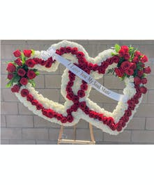 Sympathy arrangement of two hearts created with carnations and red roses.