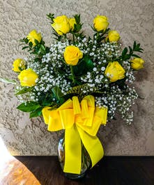 One dozen yellow roses and baby's breath in a clear glass vase tied with yellow ribbon.