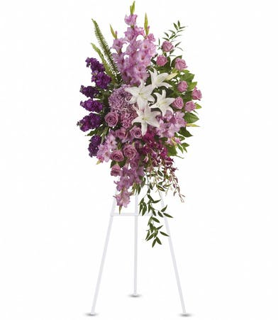 Sympathy spray of lavender, purple and white flowers.