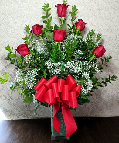 6 Long stemmed red roses in a clear glass vase.