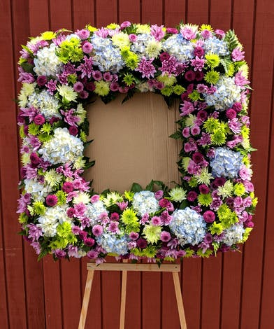 Sympathy wreath of blue hydrangea, green mums, purple button mums and lavender chrysanthemums to surround a photograph.