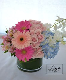 Light pink and blue flowers in a green cylinder vase.